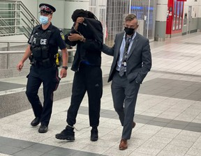 Malik Essue, 23, being escorted through Toronto Peearson Airport Thursday evening, back in Peel Region after being arrested in Fort McMurray in connection with the 2020 murder of Santiga Sharma. He's charged with first-degree murder.