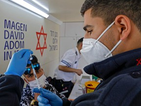 A paramedic with Israel's Magen David Adom medical services prepares a dose of the Pfizer-BioNTech COVID-19 vaccine to inoculate a Palestinian man in a mobile clinic on Feb. 26, 2021, at the Damascus Gate in Jerusalem's Old City.