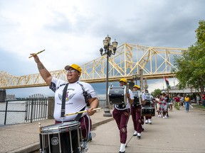 River City Drum Corps marches with a crowd following during the Juneteenth commencement of On the Banks of Freedom on June 19, 2021 in Louisville, Ky.