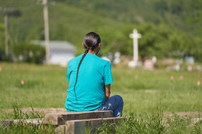 A man sits and prays at the field where the remains of over 750 children were buried on the site of the former Marieval Indian Residential School in Cowessess First Nation, Saskatchewan.