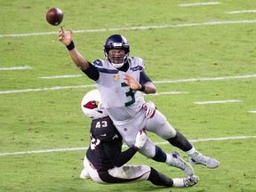 Seattle Seahawks quarterback Russell Wilson (3) throws while being tackled by Arizona Cardinals outside linebacker Haason Reddick (43) at State Farm Stadium.