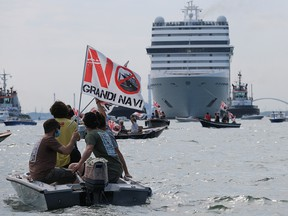 Venice residents sit on boats as they protest to demand an end to cruise ships passing through the lagoon city, as the first cruise ship of the summer season departs from the Port of Venice, Italy, June 5, 2021.