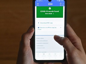 This illustration  shows a smartphone screen displaying a Covid-19 vaccine record on the National Health Service (NHS) app in London, England, on May 18, 2021.
