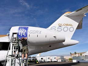 Workers apply a Rolls Royce decal to the engine of a Bombardier Global 6500 business jet at the Bombardier booth at the National Business Aviation Association (NBAA) exhibition in Las Vegas, Nevada, Oct. 21, 2019.