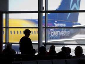 Travellers wait in the departure lounge at London International Airport to board a Transat Holidays flight to Cuba in London, Ont. March 12, 2015.