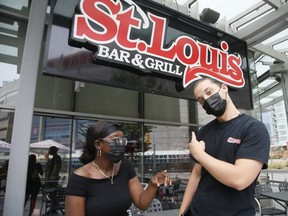 Servers Anta Owusu (left) and Griffin Rowe are pictured in front of the St. Louis Bar and Grill on July 18, 2021.