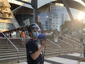 A City of Toronto worker uses a bullhorn to encourage Blue Jays fans to stop into a pop-up clinic to get vaccinated before heading into the Rogers Centre on Friday, July 30, 2021.