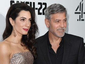 """Amal Clooney and George Clooney attend the """"Catch 22"""" U.K. premiere on May 15, 2019 in London."""