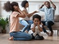 Upset african kids closing ears hurt by parents fighting