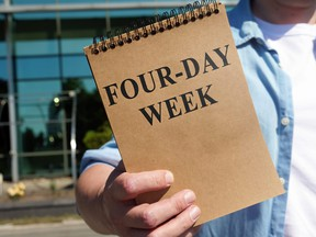 Man proposes four-day week sign. Notepad in hand.