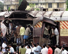 Mumbai, INDIA: (FILES) In this file photo taken, 11 July 2006, Rescue workers search for bodies inside the mangled compartment of one of the blast affected local trains at Mahim railway station in Mumbai.