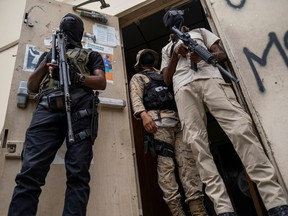 Bodyguards of former senators Steven Benoit and Youri Latortue guard the doorway outside the court house during a hearing following the assassination of President Jovenel Moise, in Port-au-Prince, Haiti July 12, 2021.