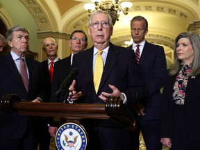 U.S. Senate Minority Leader Sen. Mitch McConnell (R-KY), centre, speaks as (left to right) Sen. Roy Blunt (R-MO), Sen. Rick Scott (R-FL), Sen. John Barrasso (R-WY), Senate Minority Whip Sen. John Thune (R-SD) and Sen. Joni Ernst (R-IA) listen during a news briefing after a weekly Senate Republican Policy Luncheon at the U.S. Capitol on July 27, 2021 in Washington, D.C.