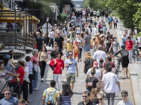 Pedestrians walk in Place Jacques-Cartier in Old Montreal, Sunday, July 4, 2021.