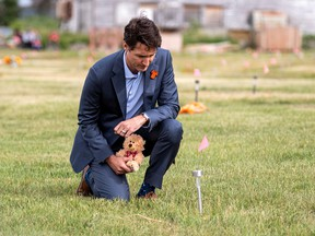 Prime Minister Justin Trudeau lays a teddy bear at a small flag in a field prior to a ceremony at the site of a former residential school, in Cowessess First Nation, Saskatchewan July 6, 2021.