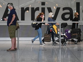 In this file photo taken on June 3, 2021 passengers push their luggage on arrival in Terminal 5 at Heathrow airport in London.