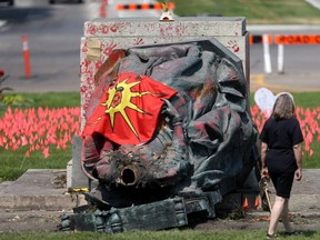 A group of protesters damaged statues of Queen Victoria and Queen Elizabeth, located on the grounds of the Manitoba Legislative Building and Government House, respectively, in Winnipeg, Thursday, July 1, 2021.