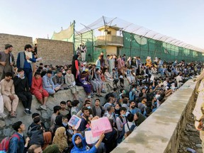 Crowds of people wait outside the airport in Kabul, Afghanistan on Aug. 25, 2021 in this picture obtained from social media.