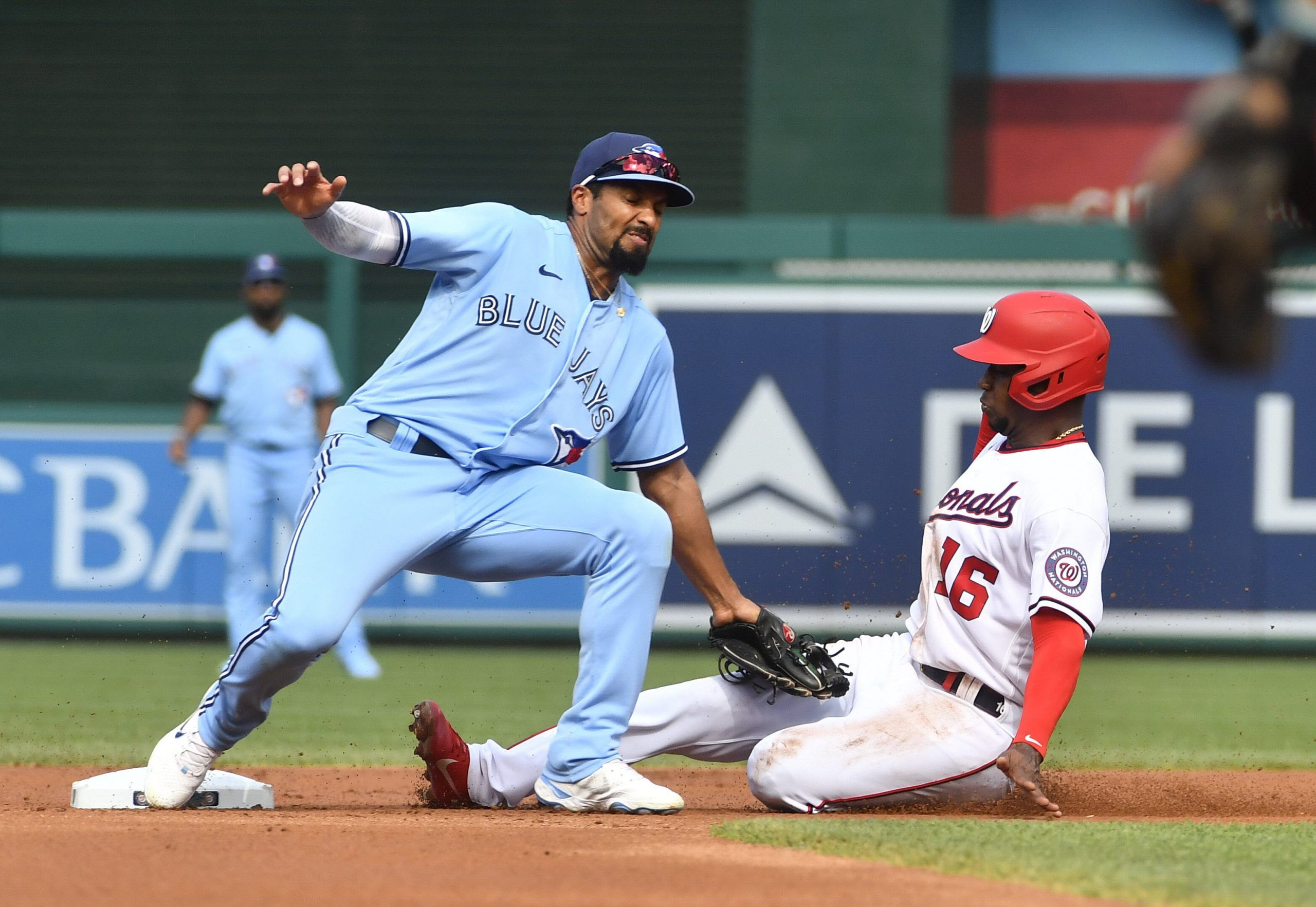 Washington Nationals' Victor Robles slides safely into second base as Blue Jays' Marcus Semien looks on during the first inning at Nationals Park on Wednesday, Aug. 18, 2021.