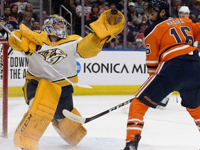 The Nashville Predators' goalie Juuse Saros makes a glove save in front of the Edmonton Oilers' Jujhar Khaira during first period NHL action at Rogers Place, in Edmonton, Feb. 8, 2020.