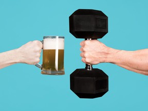 A muscular male hand holds out a heavy dumbbell towards a glass with beer in the other man s hand. Contrasting alcoholism with sports