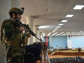 """A Taliban Fateh fighter, a """"special forces"""" unit, stands guard as Talibans acting Higher Education Minister Abdul Baqi Haqqani (not pictured) addresses a gathering during a consultative meeting on Taliban's general higher education policies at the Loya Jirga Hall in Kabul on August 29, 2021."""