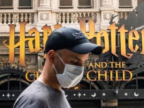 A man wears a mask to prevent against the spread of coronavirus disease (COVID-19) while he walks around Theater District in Times Square, as the highly transmissible Delta variant has led to a surge in infections, in New York City, U.S., July 30, 2021.