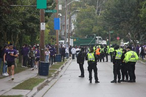 Police officers keep watch on a house party on Broughdale Avenue, near Western University, during a FoCo (Fake Homecoming) party. Photo taken Saturday Sept. 25, 2021. (Jonathan Juha/The London Free Press)