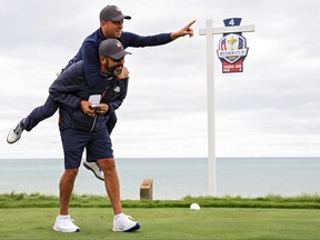 Team USA's Justin Thomas points toward the green as he jumps on the back of Michael Greller, caddie for Jordan Spieth, on the fourth tee prior to the 43rd Ryder Cup at Whistling Straits in Kohler, Wisc.