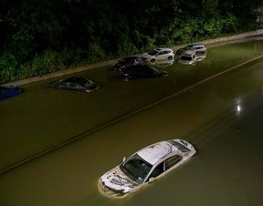 Floodwater surrounds vehicles following heavy rain on an expressway in Brooklyn, New York early on September 2, 2021, as flash flooding and record-breaking rainfall brought by the remnants of Storm Ida swept through the area.
