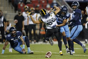 Toronto Argonauts defensive back Jeff Richards (23) separates Hamilton Tiger-Cats wide receiver Jaelon Acklin from the football in the first half of their CFL football game in Toronto, Friday, Sept. 10, 2021.
