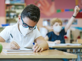 A pupil in a classroom sitting at a desk with a protective mask on the first day of school, writes in his notebook.