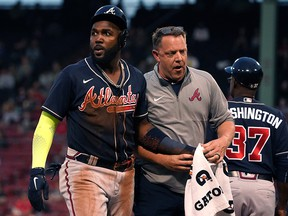 Atlanta Braves left fielder Marcell Ozuna (left) is assisted by a trainer after being injured against the Boston Red Sox at Fenway Park.