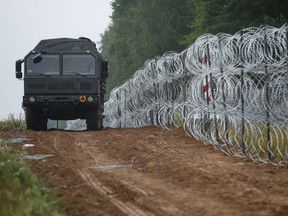 A vehicle patrols next to a fence built by Polish soldiers on the border between Poland and Belarus near the village of Nomiki, Poland August 26, 2021.