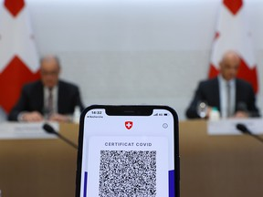 A COVID certificate is pictured on a mobile device during the news conference of Swiss Interior Minister Alain Berset and Guy Parmelin President of the Swiss Confederation on the outbreak of the coronavirus disease (COVID-19) in Bern, Switzerland, September 8, 2021.