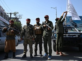 Taliban fighters stand guard along a road in Kabul on Thursday, Sept. 9, 2021.