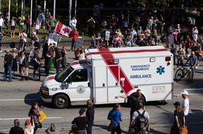 An ambulance passes through a crowd of people protesting COVID-19 vaccine passports and mandatory vaccinations for healthcare workers, in Vancouver, on Wednesday, Sept. 1, 2021. The protest began outside Vancouver General Hospital and police estimated the crowd gathered to be as many as 5,000 people.