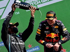 Mercedes' second placed British driver Lewis Hamilton, left, and winner, Red Bull's Dutch driver Max Verstappen, celebrate on the podium of the Zandvoort circuit after the Netherlands' Formula One Grand Prix in Zandvoort on Sept. 5, 2021.