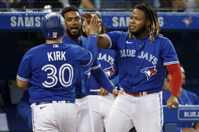 Alejandro Kirk of the Blue Jays is welcomed to the dugout by Vladimir Guerrero Jr. as he scores in the fourth inning. COLE BURSTON/GETTY IMAGES