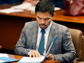 Philippine Senator and boxing champion Manny Pacquiao reads his briefing materials as he prepares for the Senate session in Pasay city, Metro Manila, Philippines September 20, 2016.