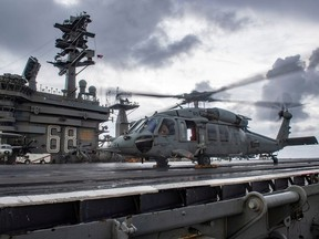 An MH-60S Sea Hawk helicopter conducts flight control checks on the flight deck of the U.S. Navy aircraft carrier USS Nimitz in the Indian Ocean November 25, 2020. Picture taken November 25, 2020.