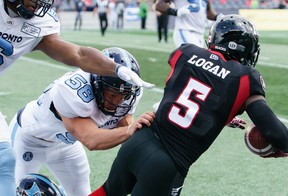 Stefan Logan #5 of the Ottawa Redblacks is pushed out of bounds by Nakas Onyeka (#6) and Jake Reinhart (#58) of the Toronto Argonauts in 2019.