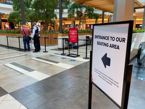 A security guard checks for proof of vaccination at the entrance to a food court during phase one of Ontario's vaccine certification program in Toronto, Sept. 22, 2021.