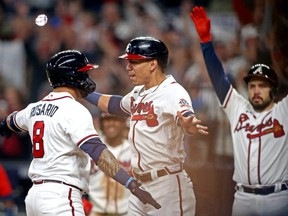 Braves left fielder Eddie Rosario (left) celebrates with third baseman Ehire Adrianza (centre) after hitting a three-run home run during the fourth inning against the Dodgers in Game 6 of the 2021 NLCS at Truist Park in Cumberland, Ga., Oct 23, 2021.