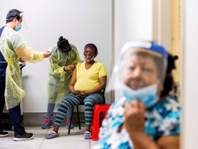 Doctor Meera Jayarajan and nurse Kevin Sagun from Humber River Hospital administer the Moderna COVID-19 vaccine to residents at a Toronto Community Housing seniors building in the northwest end of Toronto, March 25, 2021.