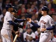 Jason Castro is congratulated by Yuli Gurriel of the Houston Astros after Castro scored in the ninth inning against the Boston Red Sox in Game 4 of the American League Championship Series at Fenway Park on Oct. 19, 2021 in Boston.
