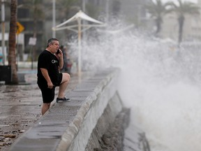 A man speaks on his mobile phone as hurricane Pamela pounds the Pacific coast resort with strong winds as it makes landfall in Mazatlan, Mexico October 13, 2021.