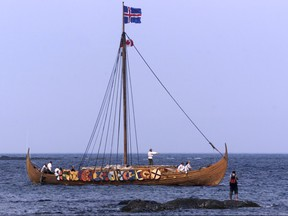 A tourist photographs the Viking replica ship the Islendingur as it arrives in the fishing village of L'Anse aux Meadows in Newfoundland, July 28, 2000.