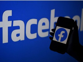 In this file illustration photo taken on April 07, 2021, a smart phone screen displays the logo of Facebook on a Facebook website background in Arlington, Virginia.