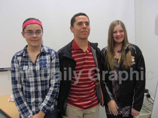 By Robin Dudgeon...EAMS grade 7 students Shae Lynn Carriere and Allie Nadeau stand with teacher Dan Rosset following Thursday's school board meeting where the girls described the school's purchase of an Automated External Defibrillator (AED) and the classes participation in the Tree for Life program.